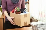 Woman packs up contents of desk. Image via shutterstock