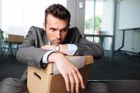 Sad man stares glumly over boxed contents of desk. Image via shutterstock (Baranq)