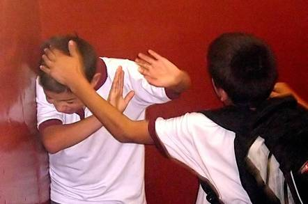 Boy slapping another boy on the head