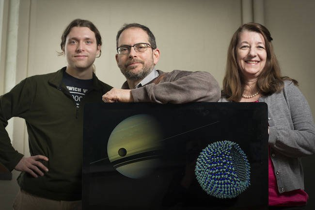 Grad James Stevenson, astronomer Jonathan Lunine and chemical engineer Paulette Clancy, with a Cassini image of Titan in the foreground of Saturn, and an azotosome, the theorised cell membrane on Titan. Credit: Cornell University