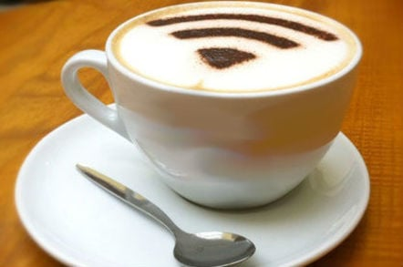 a coffee cup topped with cappucino foam with a wi-fi symbol sprinkled on top in powdered chocolate
