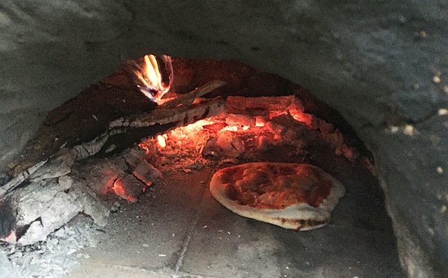 A pizza in a wood-fired oven