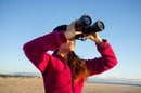 woman binoculars photo via Shutterstock