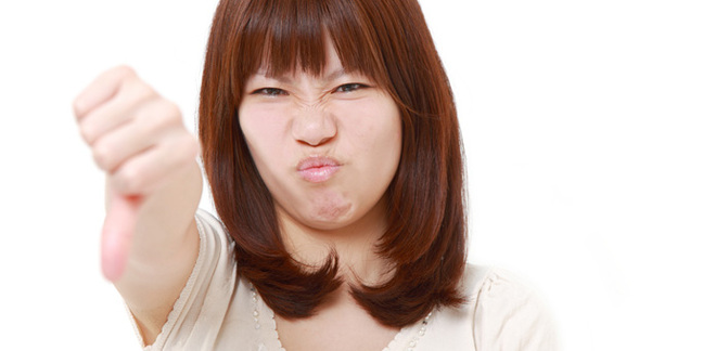 Woman thumbs down, image via Shutterstock