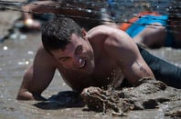 US Navy man crawling under barbed wire in tough mudder competition