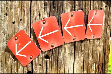 4 arrows signs in arrow on wooden wall