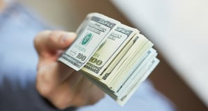 Handing over dollars picture via Shutterstock