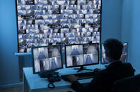 security chap watches footage of multiple cctv feeds