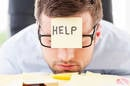 man sinks face onto pile of papers... has yellow sticky note reading help on forehead