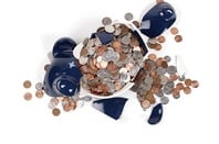 Broken piggy bank with coins surrounding it. Image via Shutterstock