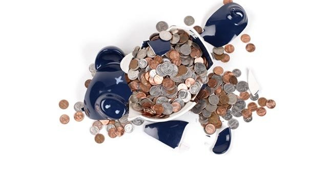 Broken piggy bank with coins surrounding it. Image via Shutterstock