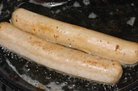 Two bratwurst frying in the pan