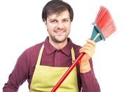 Househusband: Man in apron wields broom. Image via Shutterstock