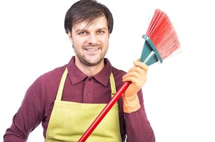 Househusband: Man in apron wields broom. Image via Shutterstock