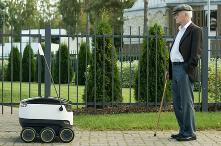 A Starship bot face-tp-face with a pensioner on the street