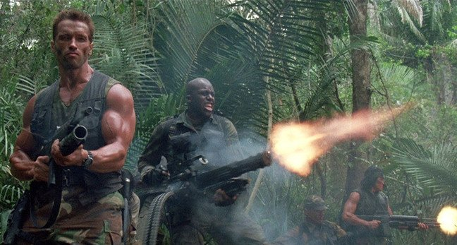 Still from Predator showing Arnie holding the M-16