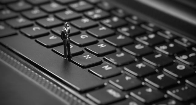 Tiny toy policeman inspects keyboard. Image via Shutterstock