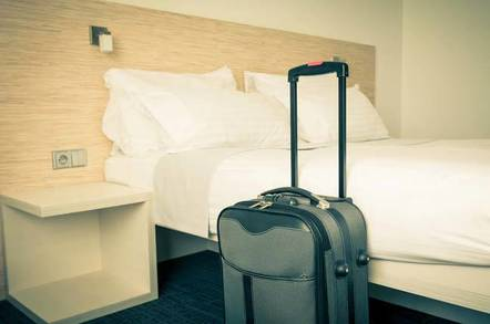 Hotel scene - suitcase propped up against freshly made bed. Image by Shutterstock