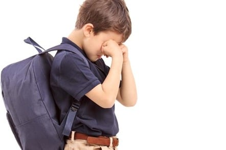 Boy with a backpack hides his eyes and cries. Pic by Shutterstock