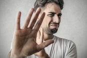 Disgusted man holds his hand up to obscure his view. Pic via Shutterstock