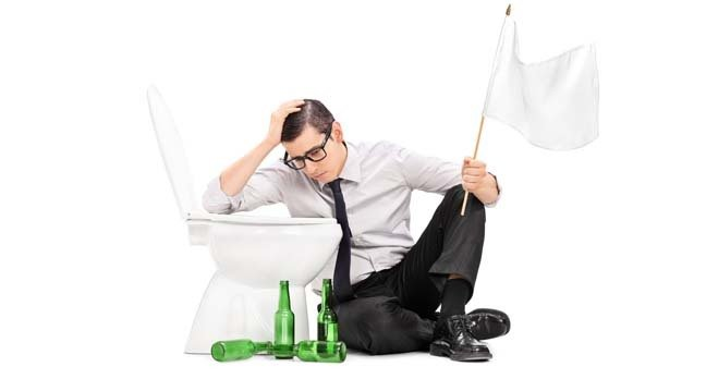 Man holds white flag while sitting alongside empty beer bottles next to a toilet bowl. Pic by Shutterstock