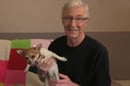 Paul O' Grady poses with a small dog.