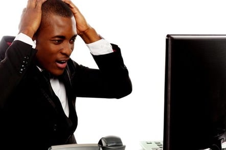 Irritated man looks at office desktop screen in frustration. Photo by Shutterstock