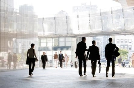 Business types walk around in a city centre square. Photo by Shutterstock