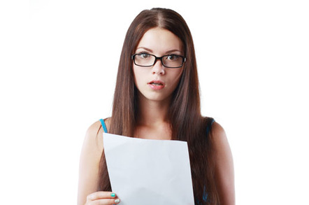 A shocked-looking woman reads a letter containing bad news. Photo via Shutterstock