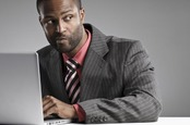 Man looks suspiciously over his shoulder while working on laptop. Photo via Shutterstock