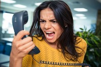 Angry businesswoman shouting on phone in office. Image via Shutterstock