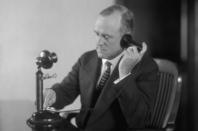 Man on old phone, image via Shutterstock