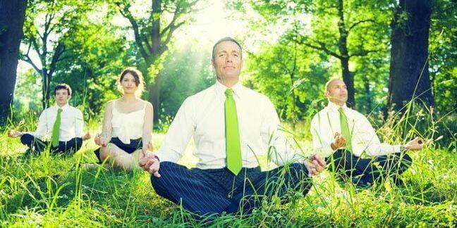 Business types meditate in green field. Photo via Shutterstock