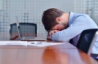 Defeated-looking young man puts his head against table in front of laptop and pile of papers in conference room. Pic via Shutterstock