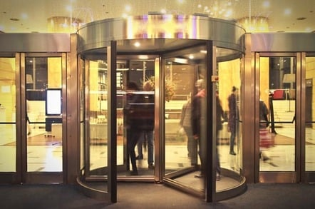 Business people move through revolving door. Photo via Shutterstock
