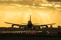 Boeing 747 lands at dusk. Photo via Shutterstock