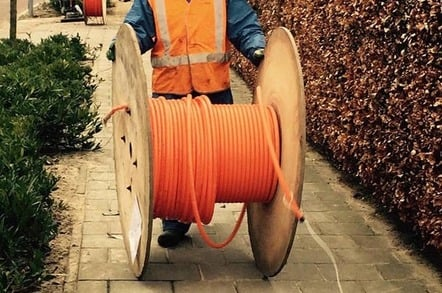Man rools out fibre cable from a large wooden cable reel on a suburban street. Pic via Pixabay