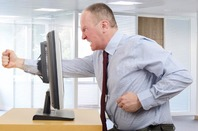 Furious man punches monitor and puts fist clear through it. Pic by Shutterstock