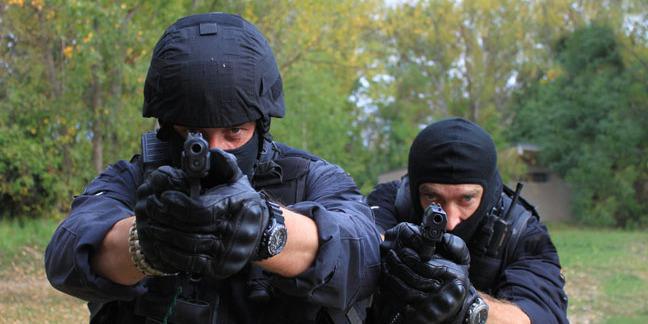 Cops with guns, image via Shutterstock