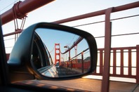 A view of the Golden Gate Bridge at sunset from the rear view mirror of a car. Pic via Shutterstock