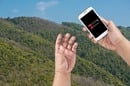 Hiker checks dead battery on smartphone... against wild valley backdrop. Photo via Shutterstock