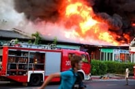 Man runs as a fire engine pulls up to a burning building. Pic by Shutterstock