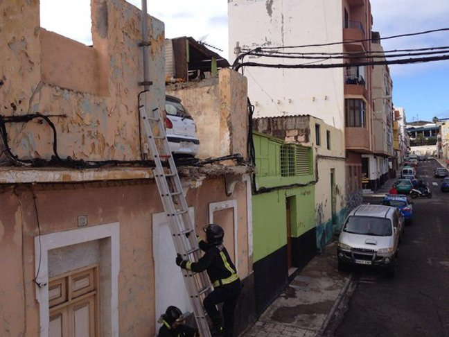 A fireman scales a ladder to the car parked on a first-floor rooftop
