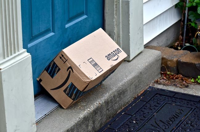 Amazon box tipped over, propped against doorframe.Photo by Jeramey Lende via Shutterstock