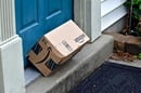 Amazon box tipped over, propped against doorframe. Photo by Jeramey Lende via Shutterstock