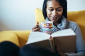 Woman reads book, sips tea on couch. Photo by Shutterstock