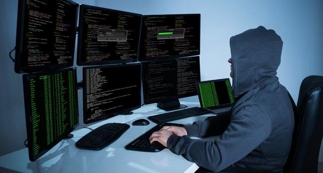 Hacker with face obscured, wearing a hoodie,  works in front of a bank of monitors. photo by Shutterstock