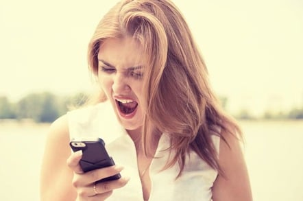 Woman angrily hangs up phone. Photo via Shutterstock