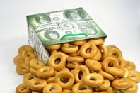 Bread/pretzels in the shape of zeros tumble out of a paper packet. photo via sHutterstock