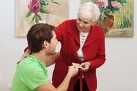 A grandmother gives cash to grandson. Photo by Shutterstock